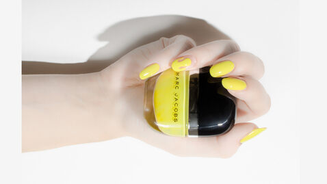 Hand with nails painted yellow holding nail polish